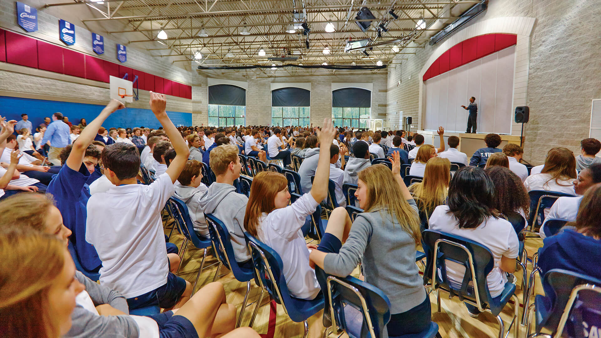 students enthusiastically raising their hands in an assembly